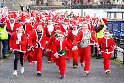 Large group of people dressed as Santas running down path