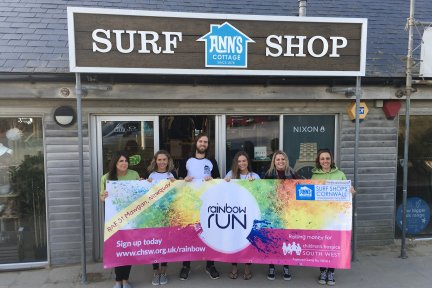 Ann's Cottage and CHSW staff launch their partnership for the Rainbow Run with a photo at the Anns Cottage store on Fistral beach