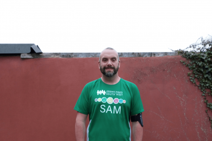 Man in green tshirt standing in garden