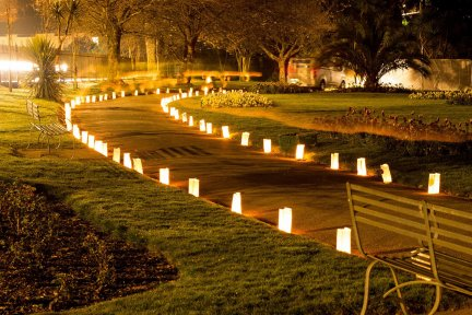 A footpath lit by candle bags at night