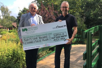 Andy Nash presents his fundraising cheque to Children's Hospice South West co-founder and chief executive Eddie Farwell at Little Bridge House