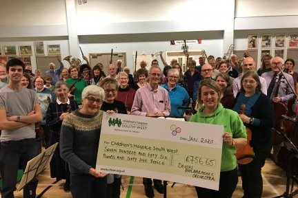 Members of the Devon Philharmonic Orchestra present the money raised to Children's Hospice South West community fundraiser Laura Robertson
