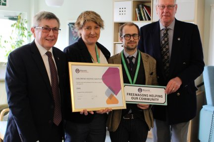 Charles Yelland and Clive Eden present the grant to CHSW fundraisers Emma Perry and Dominic Scotting