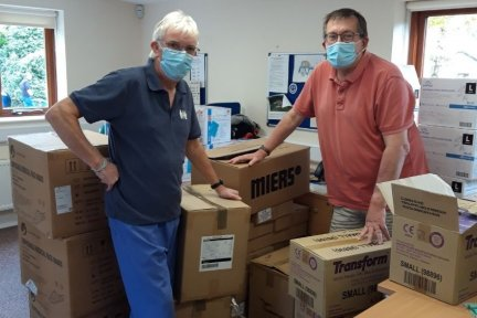Volunteers Steve Warner and Lionel Murphy processing boxes of PPE supplies at Little Bridge House