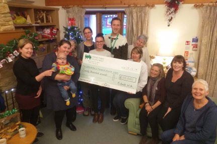 Rachel Cridge and Henry Dunn present the £20,000 fundraising cheque to the team at Little Bridge House during their stay in December