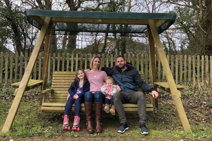 Family of four sitting on garden swing bench