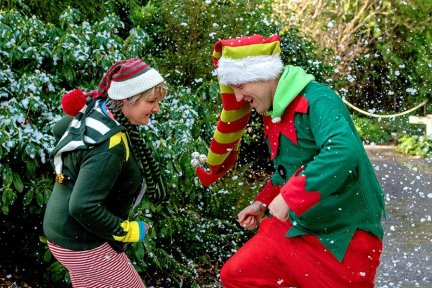 Two people dressed as Christmas elves