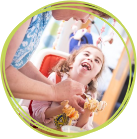 Smiling girl making cakes with her carer