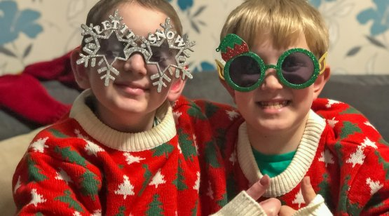 Children dressed in Christmas outfits and funny glasses
