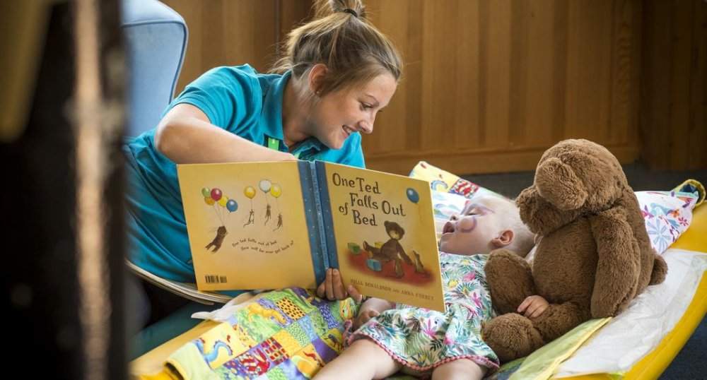 Girl with carer reading storybook