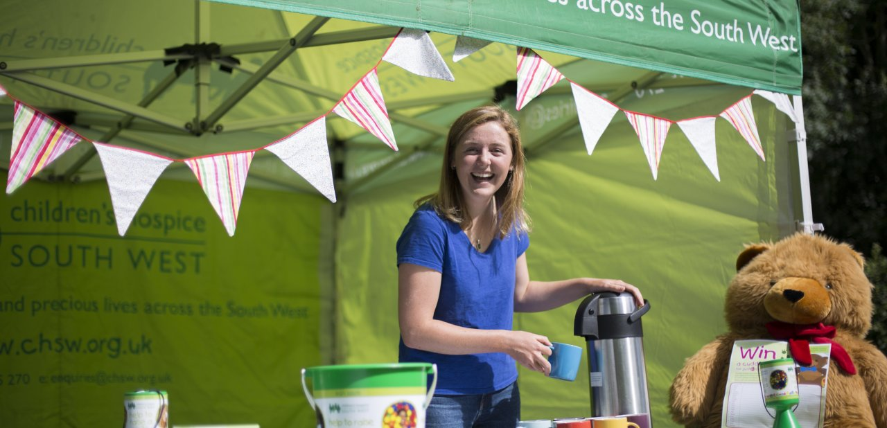 Smiling volunteer in tent pouring a hot drink