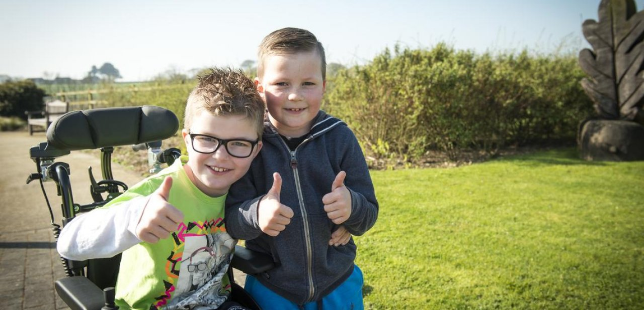 Brothers in the garden with thumbs up