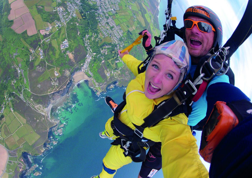 Lady skydiving over Cornish coastline