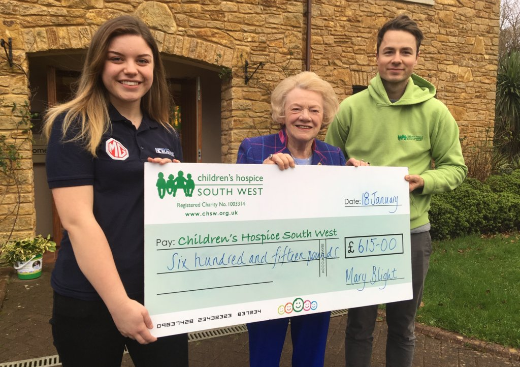 Mary Blight and Blights Motors service advisor Hannah Esau present the fundraising cheque to Children's Hospice South West community fundraiser Josh Allan at Little Bridge House in Fremington.