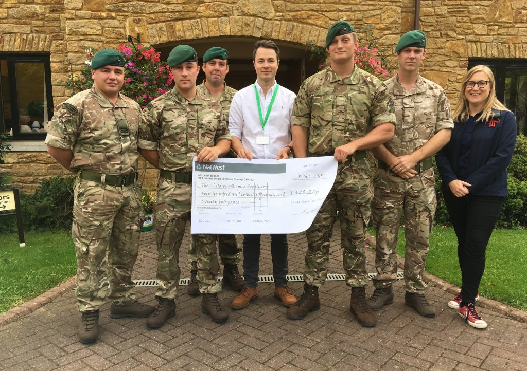 Sergeant Joe Long and colleagues from 1 Assault Group present a fundraising cheque to Children's Hospice South West community fundraiser Josh Allen at the charity's Little Bridge House