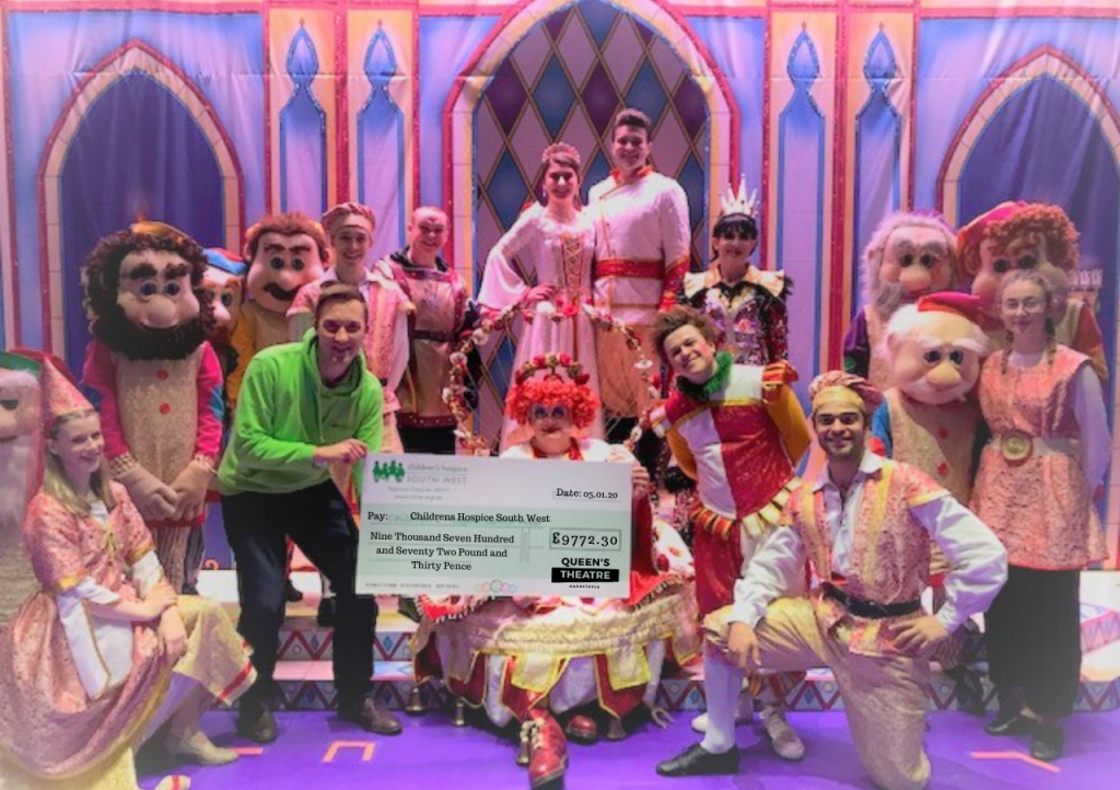 CHSW community fundraiser Neville Pope accepts the cheque from the cast of Snow White and the Seven Dwarfs at the Queen's Theatre in Barnstaple