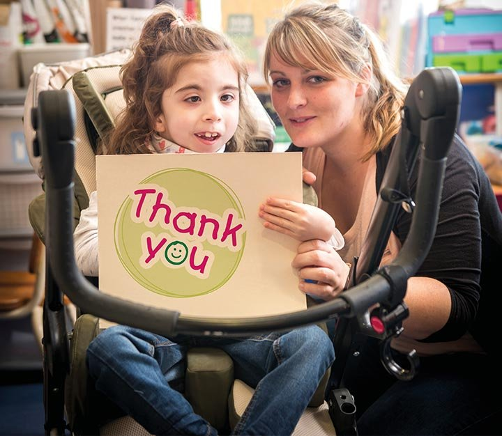 Girl in wheelchair with carer saying thank you