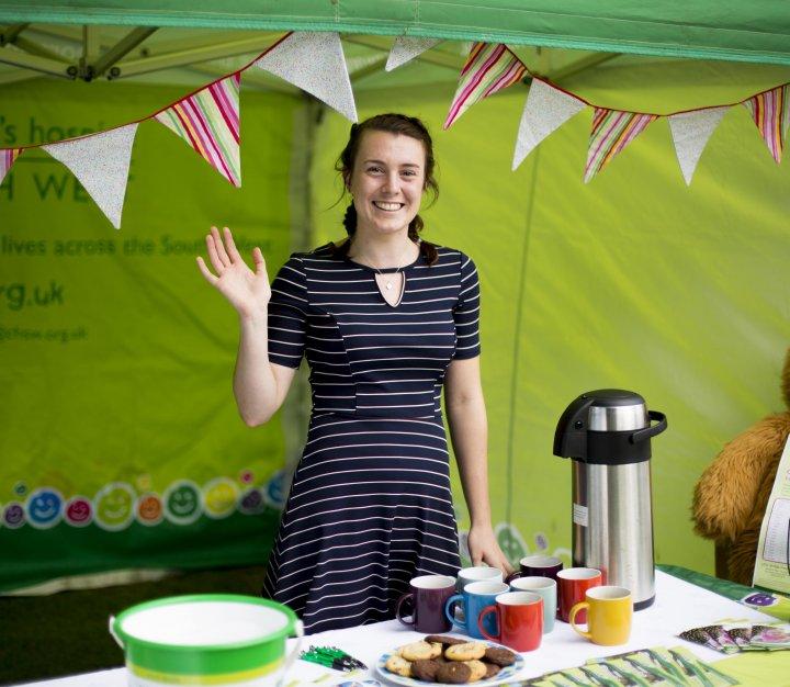 Smiling volunteer in tent stall selling hot drinks