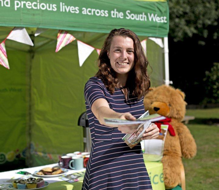 Smiling volunteer handing out leaflets