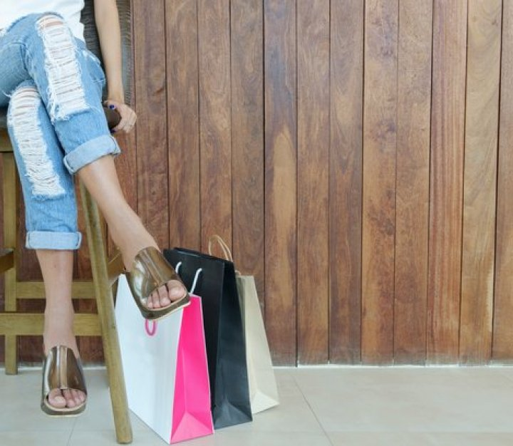 Girl sitting on stool with ripped jeans and lots of shopping bags